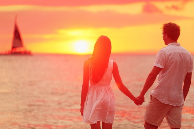 Honeymoon couple romantic in love holding hands at beach sunset.